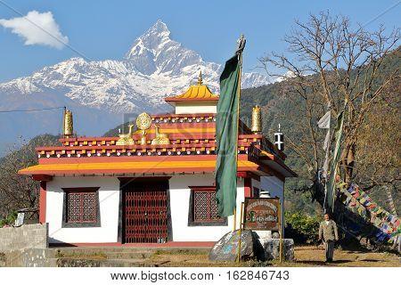 POKHARA, NEPAL - JANUARY 10, 2015: Tibetan Tashi Gang Maha Guru temple (with Machapuchare peak in the background) near Pokhara