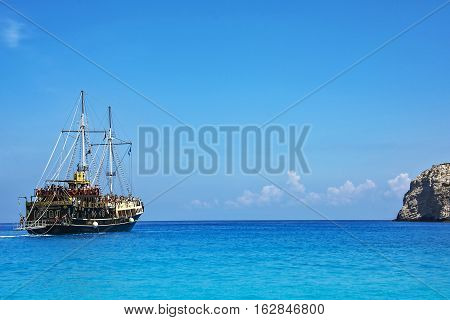 Zakynthos Island Greece - 09/06/2016: Tourists on a seagoing vessel stylized old ship sailing on the sea