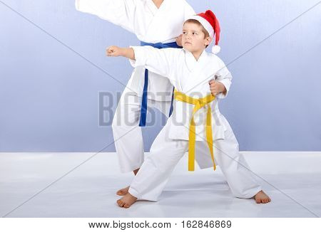 Sportsmen in the cap of Santa Claus are training punch arm
