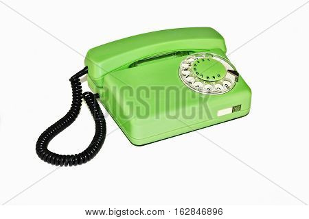 On a white background is an old telephone with a rotary dialer