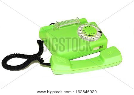 On a white background is an old telephone with a round dialer
