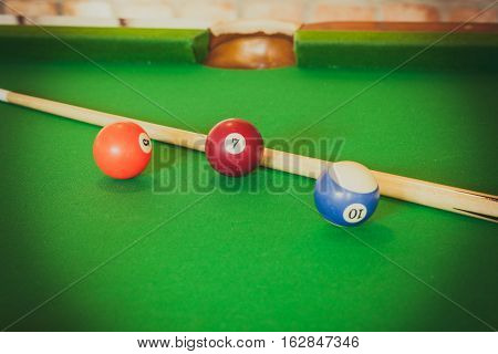 Billiard balls and cue stick on green table. Pool game