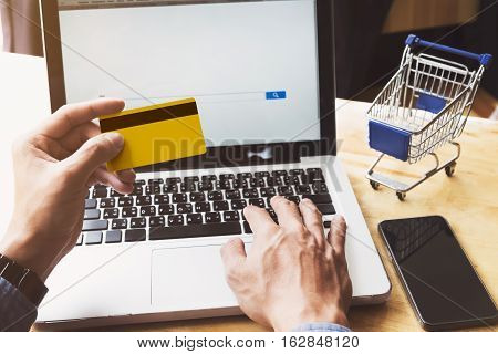 Man using laptop to online shopping and pay by credit card. Vintage tone Retro filter effect. Business and sale concept .