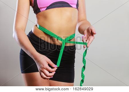 Weight loss slim body healthy lifestyle concept. Fit fitness woman in sportswear measuring her belly with green measure tape