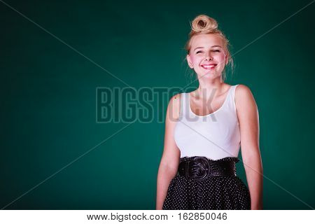Hairstyling feminity female beauty concept. Beautiful smiling teenager young woman with pin up hair. Studio shot on green background.