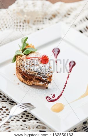 A sweet dessert consisting of crumble with applesauce and cherry topping served on a white plate
