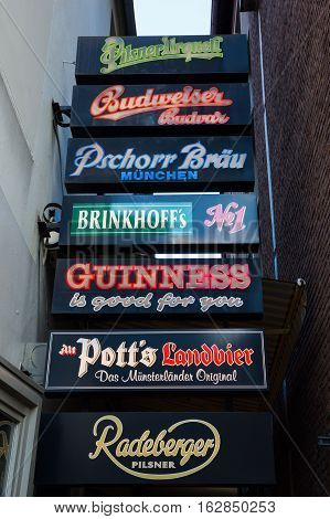 Muenster Germany - September 25 2016: pub at the Prinzipalmarkt with neon signs of several beer labels. Prinzipalmarkt is the historic principal marketplace of Muenster shaped by historic buildings