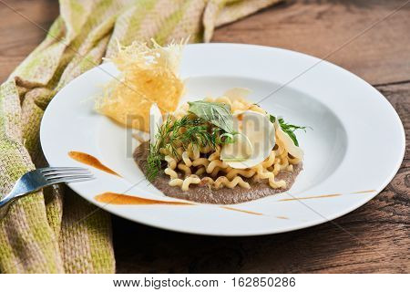 Dinner pasta fusilli with mushroom sauce served on a white plate
