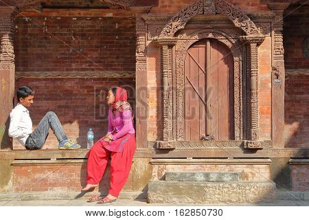KATHMANDU, NEPAL - JANUARY 14, 2015: A Nepalese couple sitting in front of a temple at Durbar Square