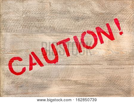 The word Caution written in red across a wooden crate