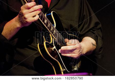 electric guitar player live on stage, band