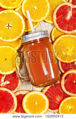 Tasty Colorful Citrus Juice in Mason Jar on Fruity Background with Citrus Slices. Top view. Healthy food.
