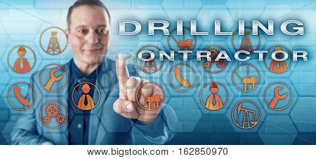 Cheerful experienced male engineer with toothless smile is pressing DRILLING CONTRACTOR on an interactive touch screen interface. Oil and gas industry metaphor and industrial services concept.