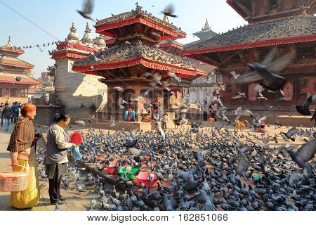 KATHMANDU, NEPAL - JANUARY 14, 2015: Two Nepalese women feeding pigeons at Durbar Square in Kathmandu, Nepal