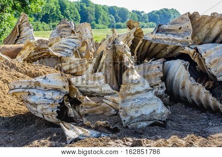 Closeup of old and dirty corrugated steel distorted and piled in a nature reserve.
