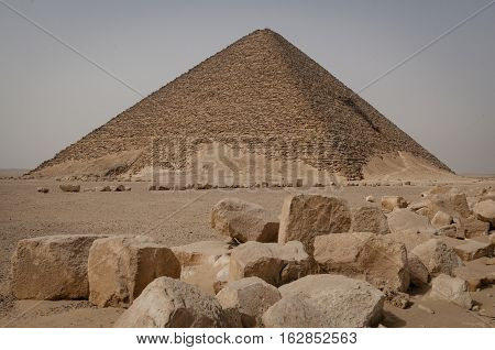 Old pyramid in the desert with stones in front of it