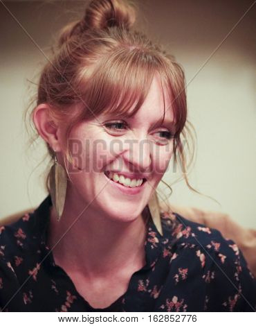 A Gorgeous Smiling Red Haired Woman with Her Hair Up and Leaf Earrings