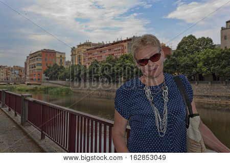 A woman of mature age in sunglasses on the waterfront of Girona