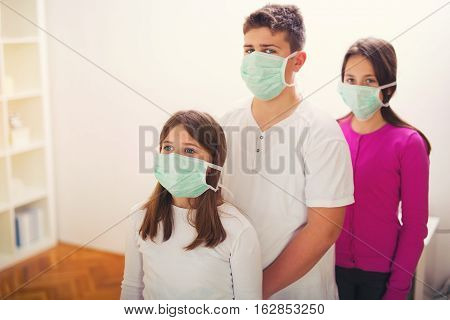 Patient teenagers looking at camera wear protective masks.