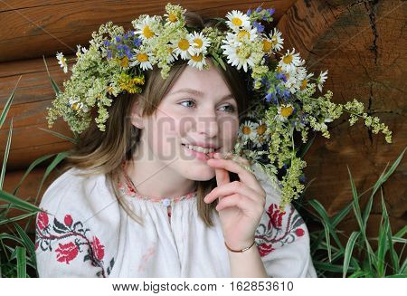 Portrait of a young girl of European appearance in the Russian national dress in white with flower wreath on head
