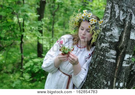 Portrait of a young Russian girl in national dress with a floral wreath on the head in the woods with strawberries