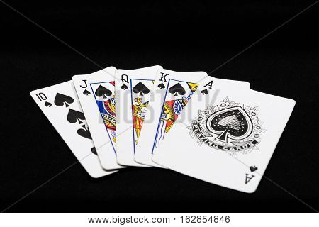 combination of royal flush of playing cards on a black background