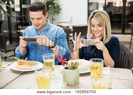 Cute Couple Taking Pictures Of Their Food