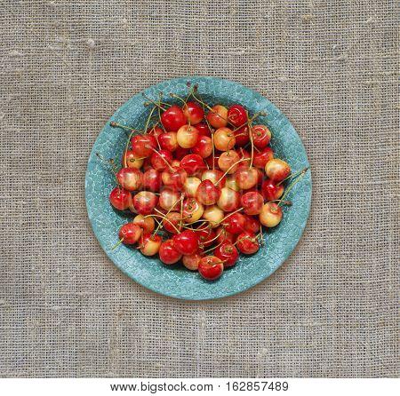 Cherry fruit. Sweet cherries in blue ceramic bowl. Top view. Ripe and tasty cherries.