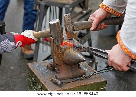 The hands of a blacksmith and learner forging hot iron on the anvil. poster
