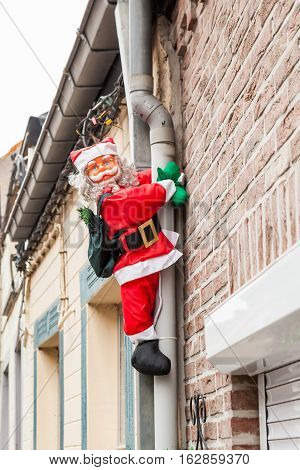 along the drainpipe next to the house Santa Claus climbs up