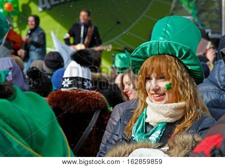 Moscow Russia - March 19 2016: Participant at the St. Patrick's Day Parade in the Irish hat and with shamrock under her eye in the park Sokolniki in Moscow