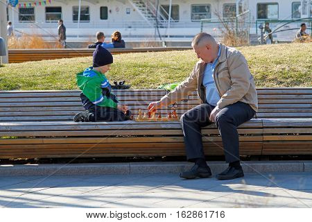 Moscow Russia - April 12 2016: Father and son playing chess in the park Muzeon in Moscow