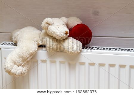 heating the house warm. radiator. teddy bear with a heart on the battery heats up sleeping