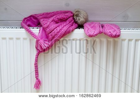 children's winter hat and mittens drying on the white iron battery. wooden wall