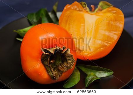 Delicious and exotic fruits of ripe persimmon in black plate, low key. Concept for healthy food, vegan or raw diet