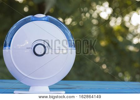 Ultrasonic humidifier in the field, expelling steam with trees in the background