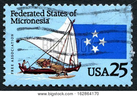 UNITED STATES OF AMERICA - CIRCA 1996: A used postage stamp from the USA depicting an illustration of islanders on an outrigger sailing canoe and flag circa 1996.