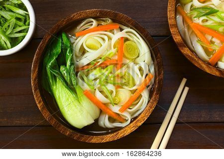 Vegetarian Asian rice noodle soup with bok choy carrots and spring onion photographed overhead on dark wood with natural light (Selective Focus Focus on the top of the soup)