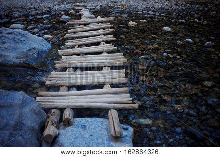 wooden makeshift bridge over a small river