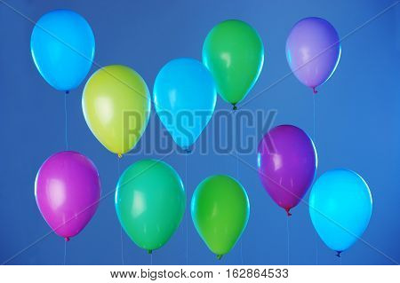 Colorful balloons arranged in two rows on dark blue background