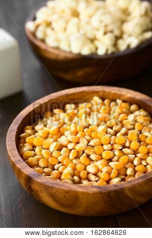 Yellow raw popcorn kernels in wooden bowl with salted popped popcorn in the back photographed with natural light (Selective Focus Focus in the middle of the kernels)
