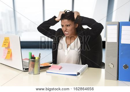 young beautiful latin businesswoman suffering stress working at office computer desk looking worried and desperate having problem at work in overwork concept