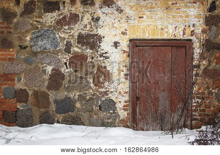 Old farmhouse with a stone wall and wooden door