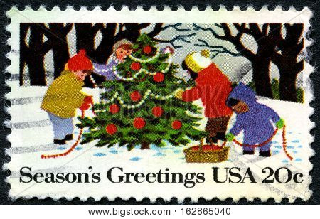 UNITED STATES OF AMERICA - CIRCA 1982: A used postage stamp from the USA celebrating the Christmas season with an illustration of children decorating a Christmas tree circa 1982.