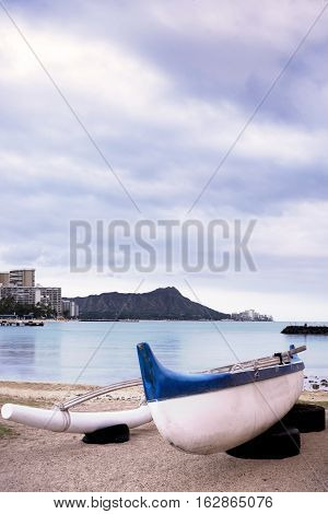 Outrigger canoe on beach with Diamond Head in the background