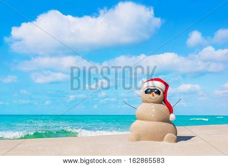Positive sandy snowman in red Santa Claus hat and eyeglasses at cloudy sunny ocean beach. Happy New Year and Merry Christmas travel destinations concept for tropical vacations.