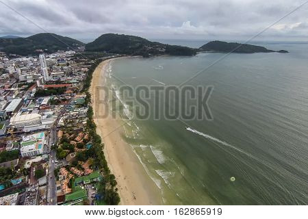 Aerial view of Patong Beach in Phuket, Thailand with parasailers, jetskis, and tourists below