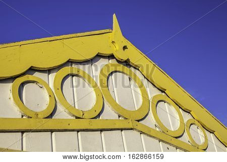 Yellow wooden fascia board with circle decoration on a beach hut contrasting against a blue sky.