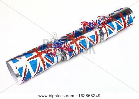A studio shot of a Union Flag Cracker or otherwise known as a Bon Bon. A traditional cracker consists of a cardboard tube wrapped in a brightly decorated twist of paper with a gift in the central chamber.