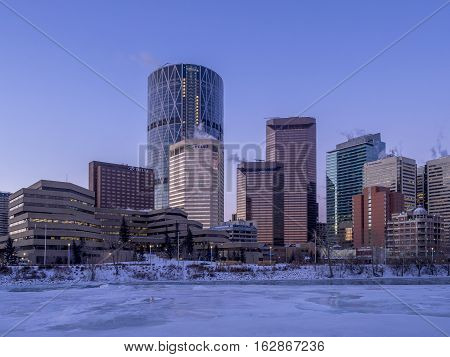 CALGARY, CANADA - DEC 17: Calgary's skyline at sunrise on a cold winter day on December 17, 2016 in Calgary, Alberta. Calgary is home to many oil companies. The Bow River is visible.